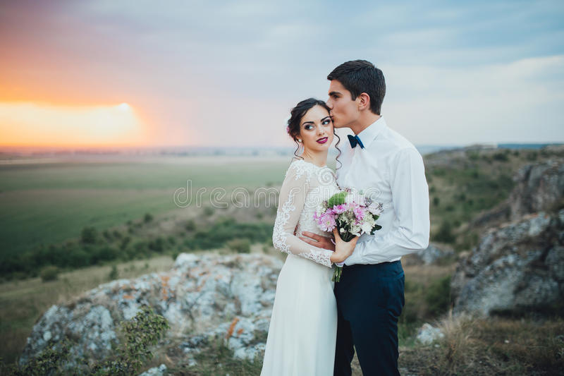 Wedding couple. In the evening. Peaceful romantic moment. Happy bride and groom on a beautiful beach on sunset. bride in a white dress holding a bouquet of royalty free stock images