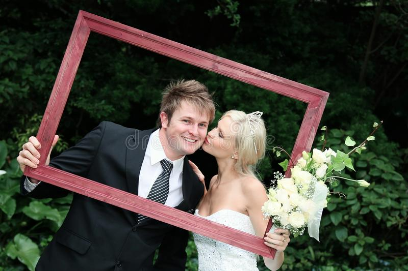 Wedding Couple in Frame. Beautiful bride kissing the smiling groom and framed by a picture frame