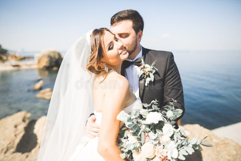 Wedding couple, groom, bride with bouquet posing near sea and blue sky.  stock photos