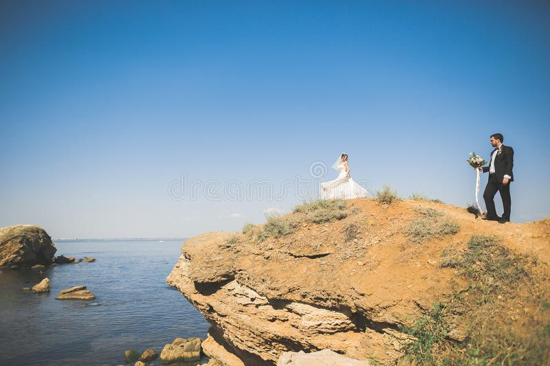 Wedding couple, groom, bride with bouquet posing near sea and blue sky.  stock images