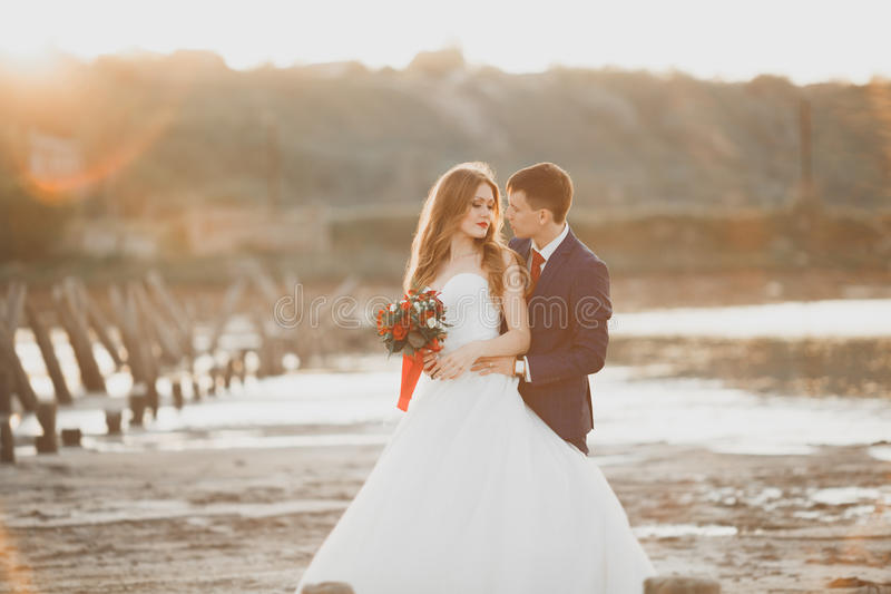 Wedding couple, groom, bride with bouquet posing near sea on sunset.  stock images