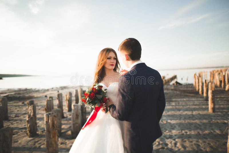 Wedding couple, groom, bride with bouquet posing near sea on sunset.  stock image