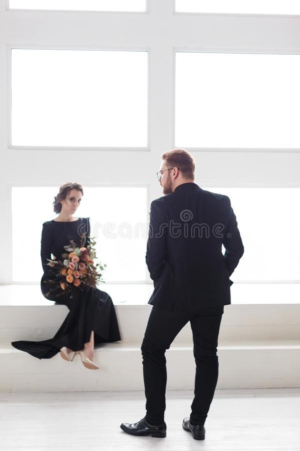 Wedding Couple Groom And Bride Posing In A White Studio. Black Suit ...