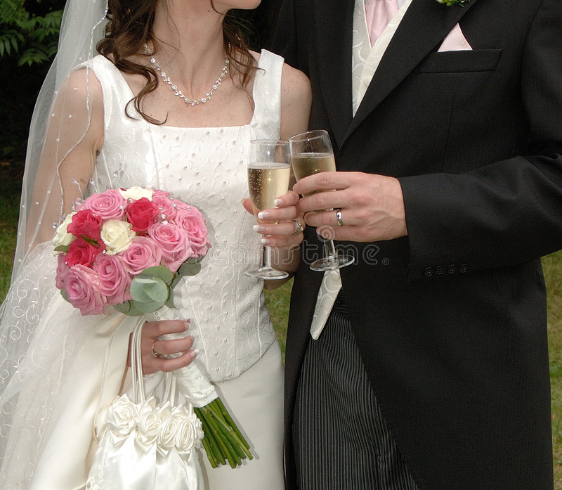 A Wedding couple holding flowers and glasses stock photography