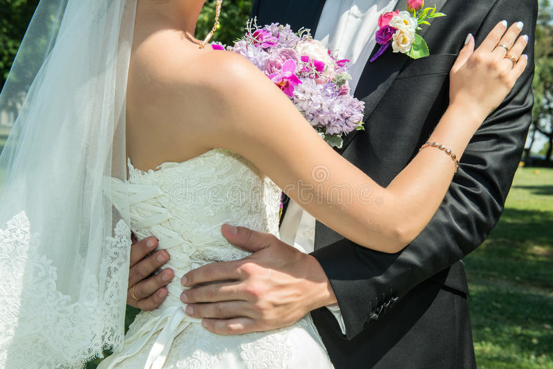 Wedding couple holding hands and hugging royalty free stock photo