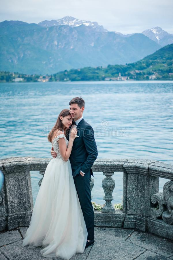 Wedding couple hugging the backdrop of lake and mountains stock images