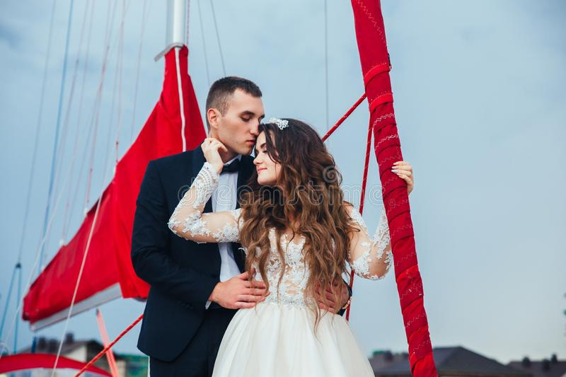 Wedding couple is hugging on a yacht. Beauty bride with groom stock image