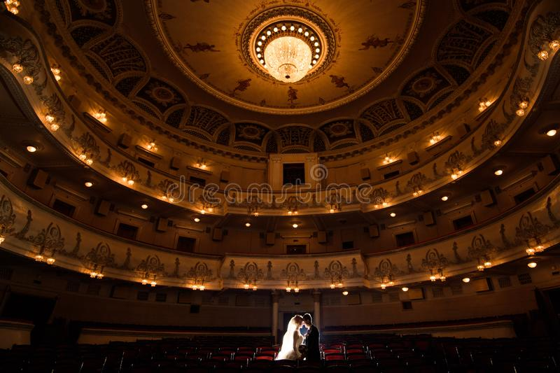 Wedding couple indoors is hugging each other. Wedding couple in drama theater.the bride and groom, love, dress, beautiful, female, young, woman, white royalty free stock photo