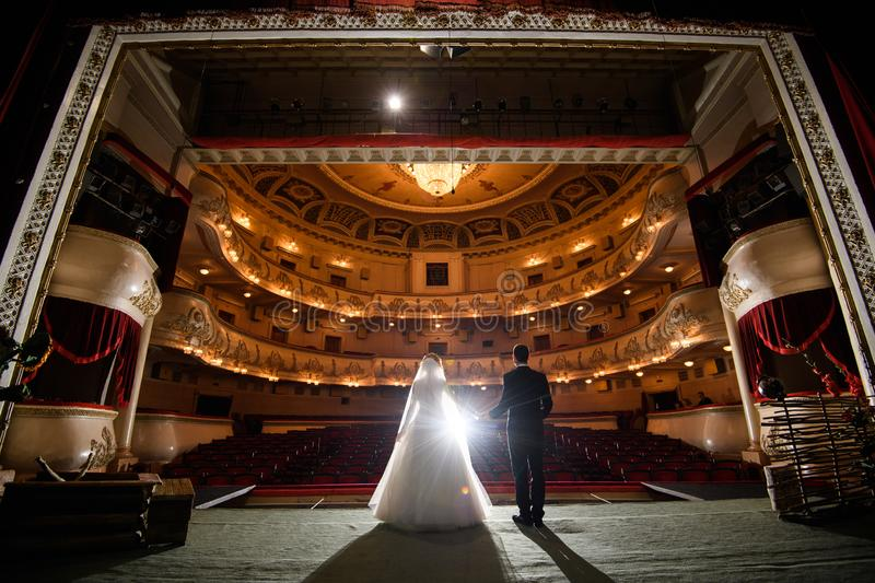 Wedding couple indoors is hugging each other. Wedding couple in drama theater.the bride and groom, love, dress, beautiful, female, young, woman, white, romantic stock image