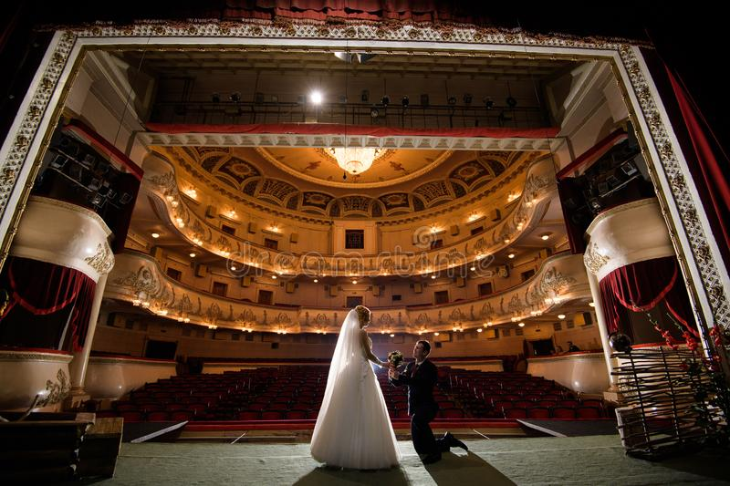 Wedding couple indoors is hugging each other. Wedding couple in drama theater.the bride and groom, love, dress, beautiful, female, young, woman, white, romantic stock photography