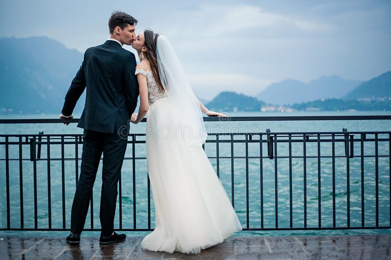 A wedding couple kissing on the background of a lake and mountains stock photography