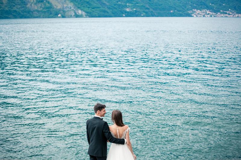 Wedding couple kissing on the background of the lake and the mountains stock photography