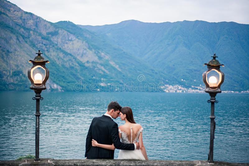 Wedding couple kissing on the background of a lake and mountains stock photo