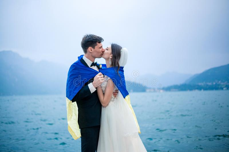 a wedding couple kissing on the background of a lake and mountains stock photos