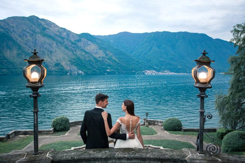Wedding couple kissing on the background of the lake and the mountains stock image