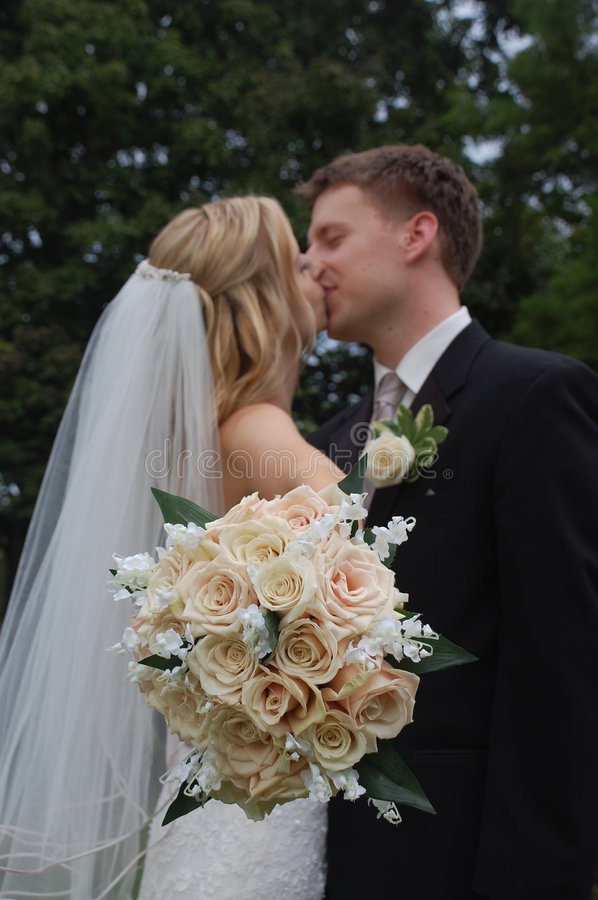 Wedding Couple Kissing with Bouquet stock image