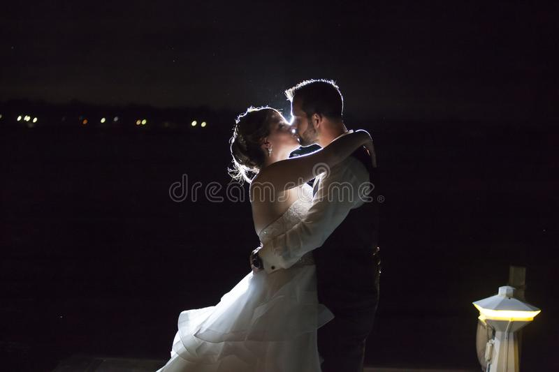 Backlit night wedding couple kissing. A wedding couple kissing on edge of river back lit by off camera flash stock photos