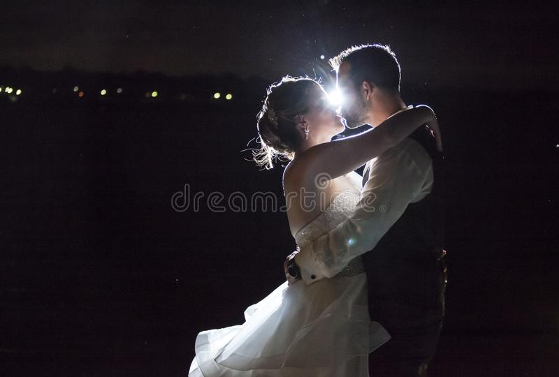 Backlit night wedding couple kissing royalty free stock images
