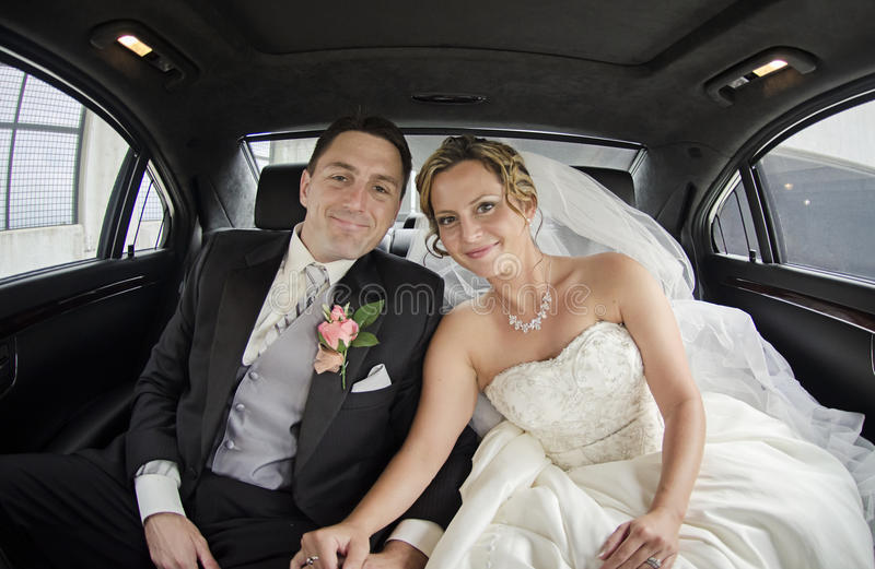 Wedding couple in Limousine. A smiling bride and groom in a limousine stock images