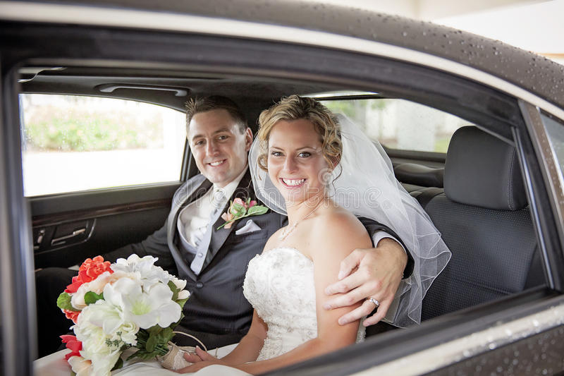 Wedding couple in Limousine. A smiling bride and groom in a limousine stock photo
