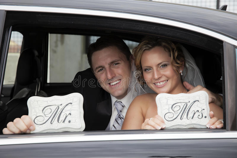 Wedding couple in Limousine. A smiling bride and groom in a limousine holding Mr and Mrs signs stock images