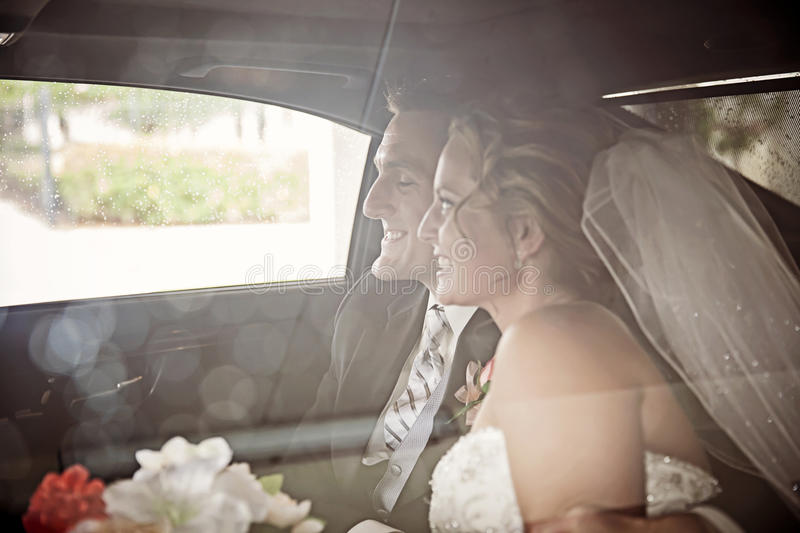 Wedding couple in Limousine. A smiling bride and groom in a limousine through rainy window stock photos