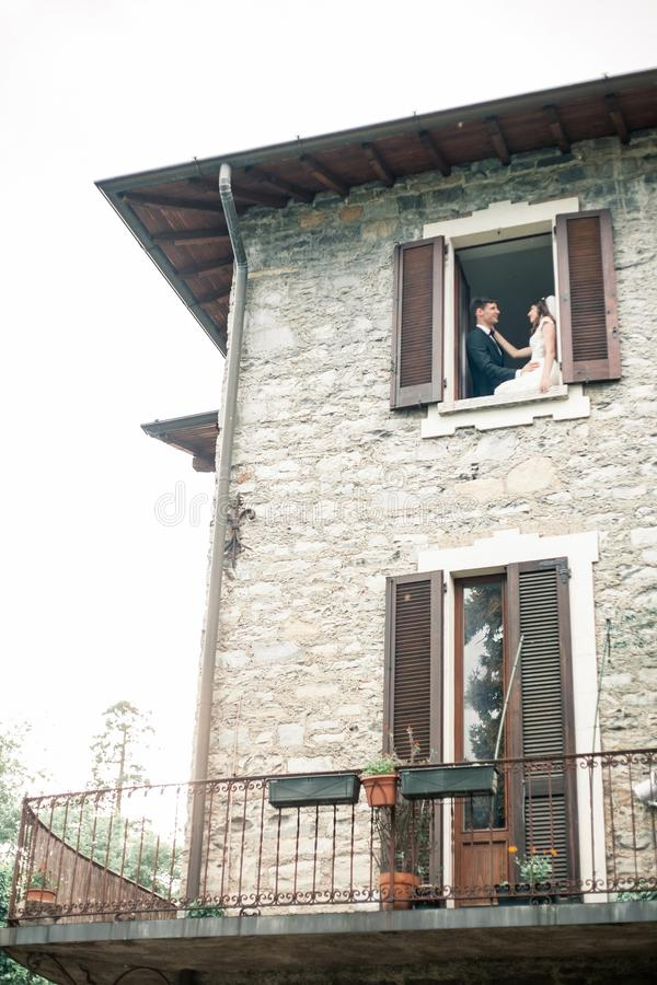 Wedding couple looks out the window of a big house stock photography