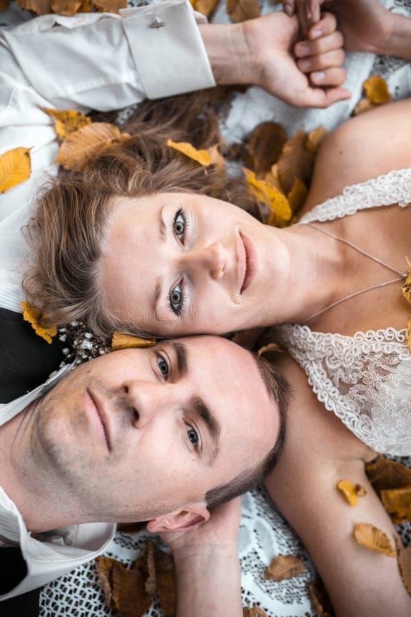 Wedding couple lying under a tree royalty free stock photos