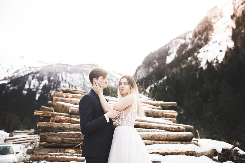 Wedding couple on the nature is hugging each other. Beautiful model girl in white dress. Man in suit stock photo