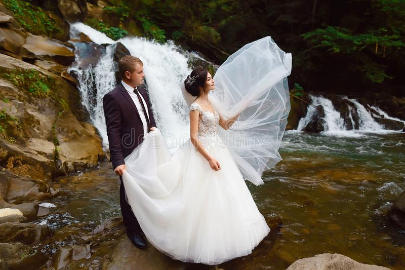 Wedding, couple near beautiful grand waterfall in mountain. Wind fluttering a long veil. Landscape of hills and mountains royalty free stock images