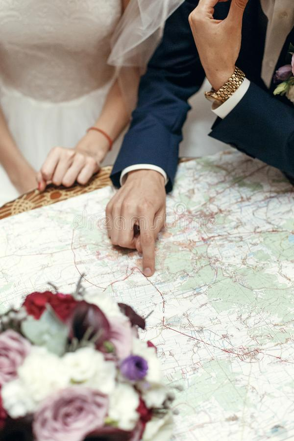wedding couple planning honeymoon. stylish bride and groom looking at map, talking about summer travel vacation, sitting stock images