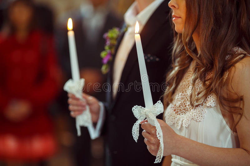 A wedding couple pray during an engagemnt ceremony holding candles in their hands stock photography