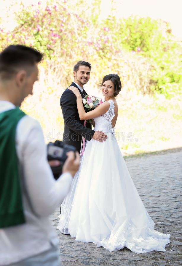 Wedding couple and professional photographer. With camera, outdoors stock photo