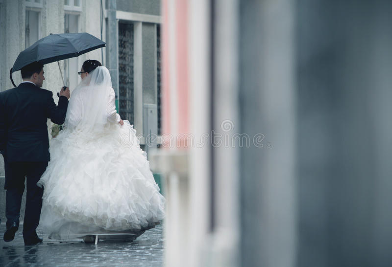 Wedding couple in rain. Walking the urban streets with umbrella stock photography