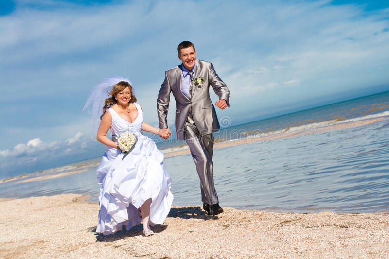 Download Wedding Couple Runs On The Beach Stock Image - Image of dress, married: 17553831
