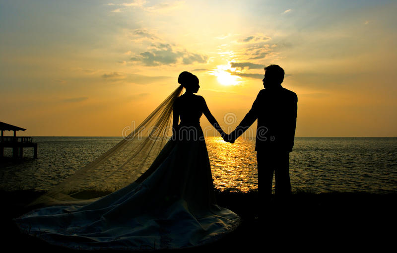 Wedding couple sillhouette at sunset. Romantic silhouette of wedding couple at sunset stock image