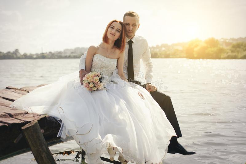 Wedding couple sitting on bridge near lake on sunset at wedding day. Bride and groom in love. Woman in white dress main white shirt and tie royalty free stock images