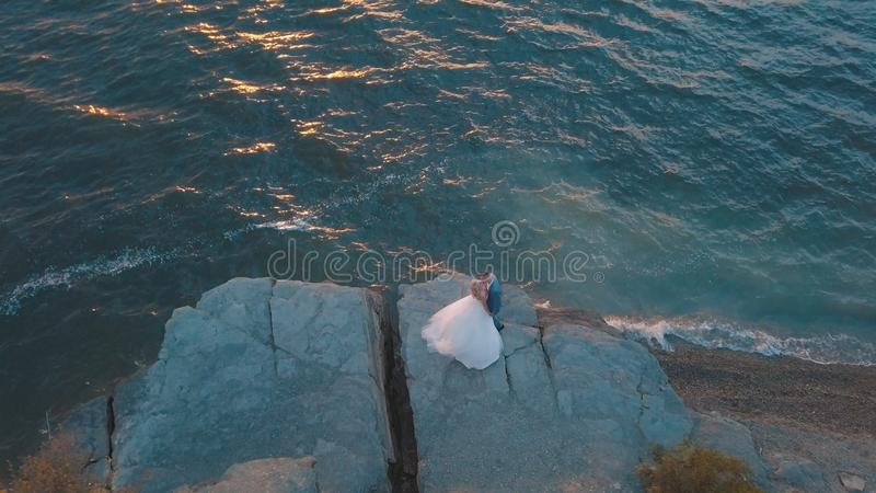 Wedding couple on a slope of the mountain hill near sea. Aerial shot royalty free stock image