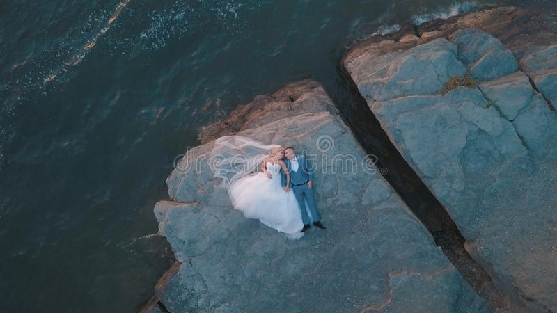 Wedding couple on a slope of the mountain hill near sea. Aerial shot royalty free stock photos