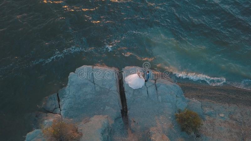 Wedding couple on a slope of the mountain hill near sea. Aerial shot royalty free stock photo