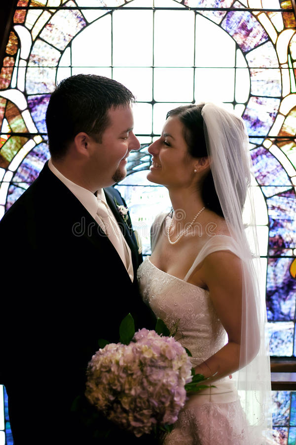 Wedding couple stained glass window. Bride and groom looking at each other in front of church stained glass window stock photo