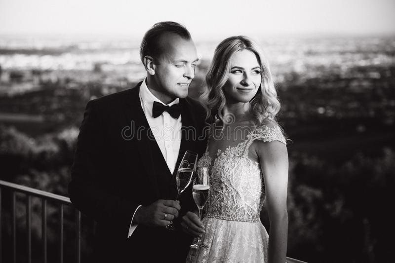 Wedding couple stand on the background of the city and drink champagne from wineglass. Black and white picture stock photos