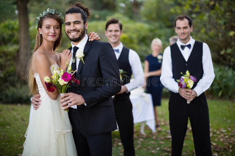 Wedding couple standing with bouquet of flowers in garden stock photography