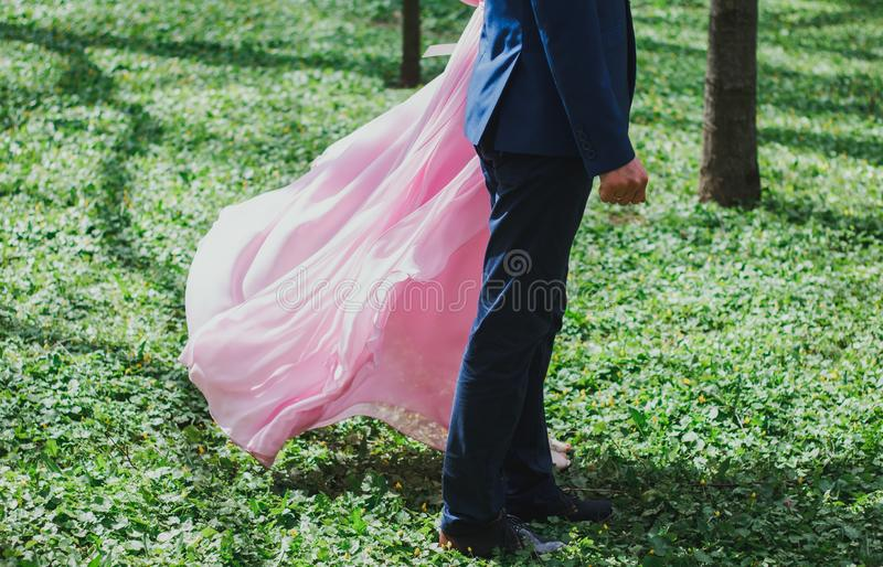 Wedding couple stands on emerald bright green grass in the summer park. Spring forest with bride and groom. Pink chiffon train royalty free stock photos