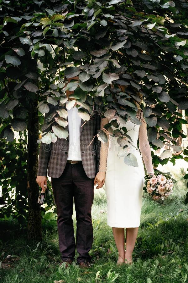 Wedding couple stands under green tree royalty free stock photos