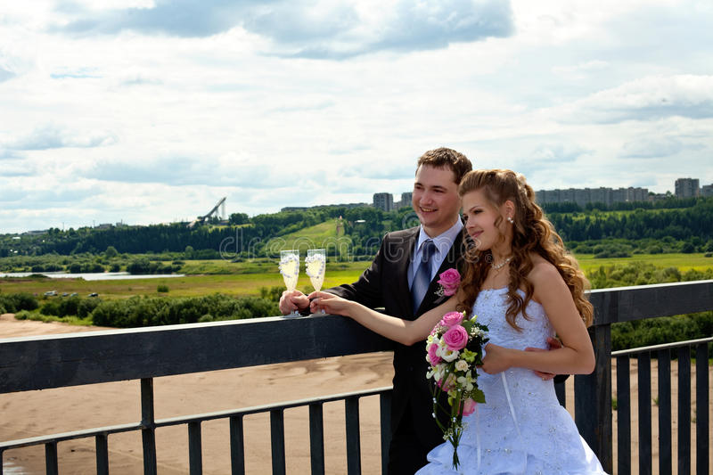 Wedding couple in sunny summer day stand on bridge stock photography