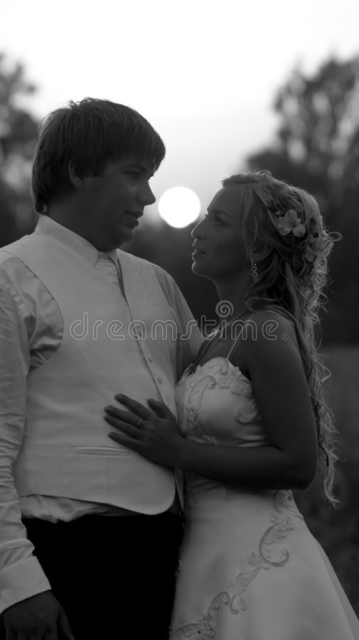 Wedding couple at sunset. A black and white view of a bride and groom together at sunset stock photos