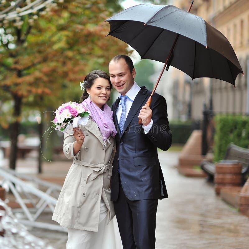 Wedding Couple Holding Umbrella In A Rainy Weather Stock