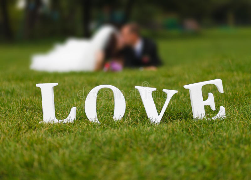 Wedding couple unfocused and love word on the grass stock photos