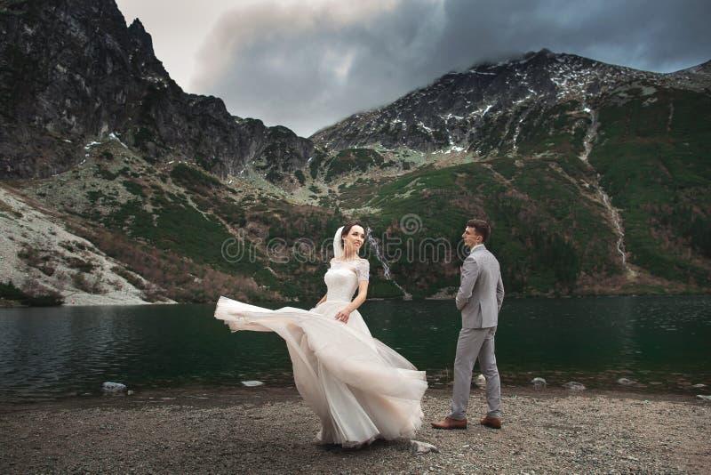 Wedding couple walking near the lake in Tatra mountains in Poland. Morskie Oko. Beautiful summer day royalty free stock photos